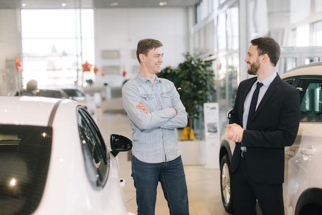 Веселый счастливый человек готовится купить новый автомобиль в автосалоне