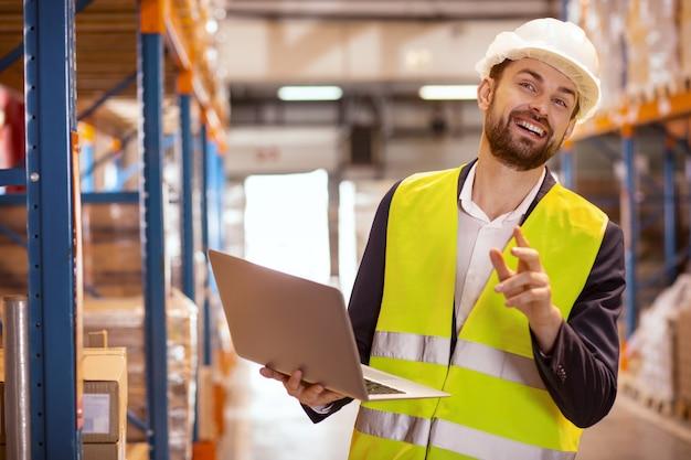 倉庫で彼の仕事を楽しみながら笑っている陽気な幸せな男