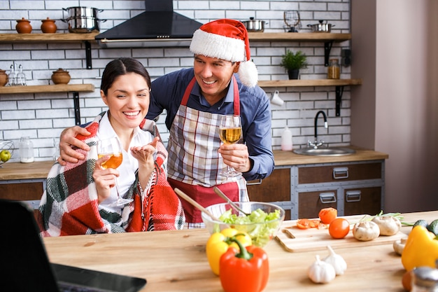 Cheerful happy man and woman celebrating christmas or new year. sitting together in room and smiling. looking at laptop. man wear hat. hold wine glasses in hands.