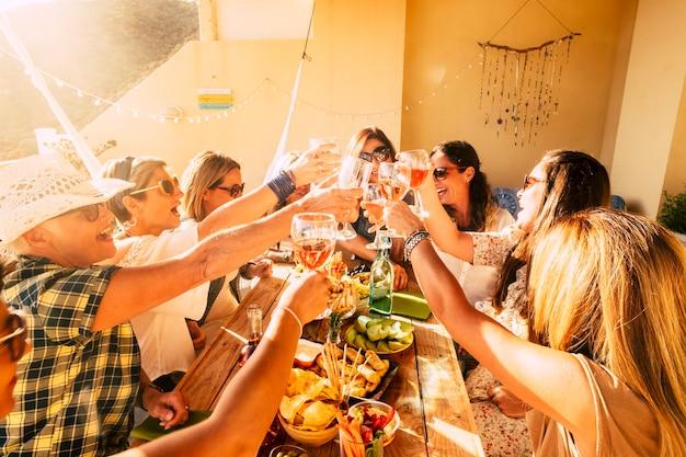 陽気な幸せな混合世代。年齢の人々女性が一緒に赤ワインのグラスをチリンと鳴らして友情を楽しんでいます-女性の友人のグループのための屋外のお祝いの余暇活動