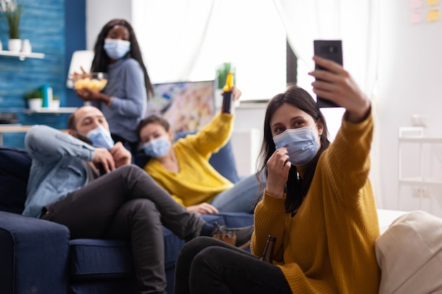Cheerful happy mixed race friends taking selfie wearing face mask keeping social distancing wearing face mask against spread of virus sitting on couch in living room. conceptual image.