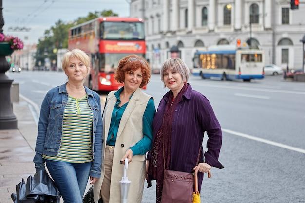 쾌활한 행복 노인은 도시 거리에 서 있고 더블 데커 버스와 함께 웃고 있습니다.