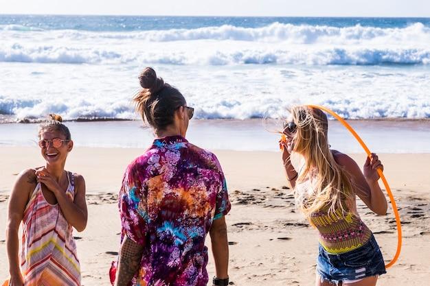 陽気な幸せな人々の白人グループは、友情で一緒に楽しんでいるビーチで夏休みの休暇を楽しんでいます