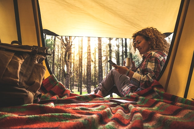 Веселые счастливые люди кавказской женщины используют сотовый телефон, сидя за пределами палатки в лесу с солнечным светом