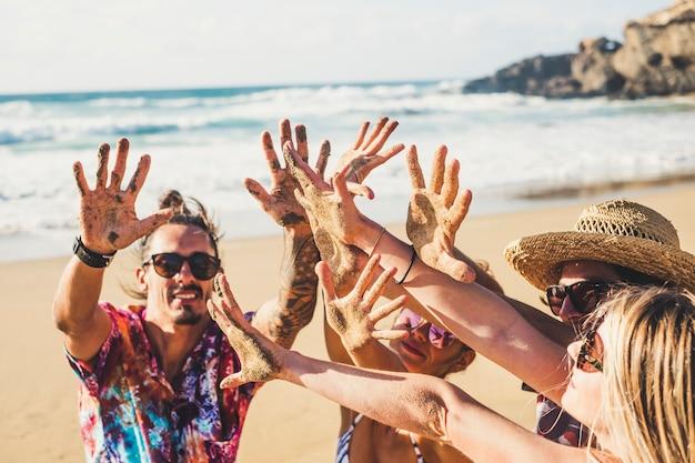 ビーチで一緒に楽しんでいる陽気な幸せな人々