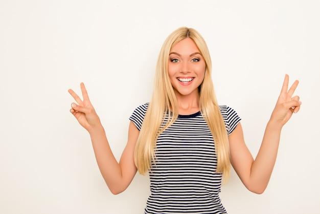 2本の指を示す陽気な幸せなかわいい女の子