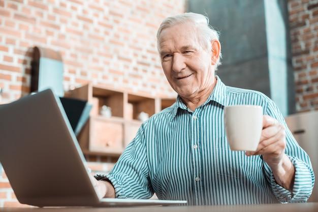 新しい技術を楽しみながら笑顔でノートパソコンの画面を見ている陽気な幸せな年配の男性