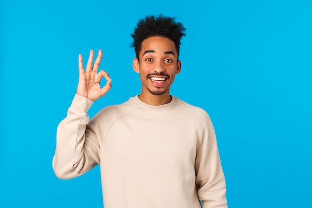 Веселый счастливый улыбающийся афроамериканец со стрижкой битника, показывающий в порядке жест и кивает в знак согласия, дает одобрение, подтверждает или соглашается участвовать, стоящая синяя стена удовлетворена