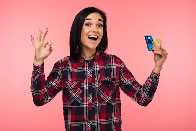 Cheerful happy surprised young woman with credit card showing sing ok over pink background