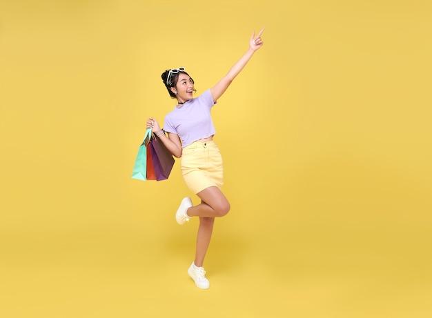 ショッピングを楽しんでいる陽気な幸せな10代のアジアの女性、彼女はショッピングセンターで最新のオファーを取得するために買い物袋と人差し指を運んでいます。 Premium写真