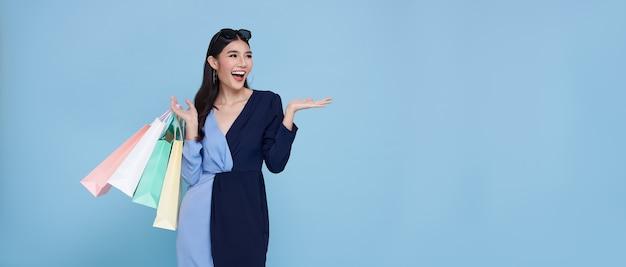 ショッピングを楽しんでいる陽気な幸せな10代のアジアの女性、彼女はコピースペースと青い背景のショッピングセンターで最新のオファーを取得するために買い物袋を運んでいます。パノラマの背景。