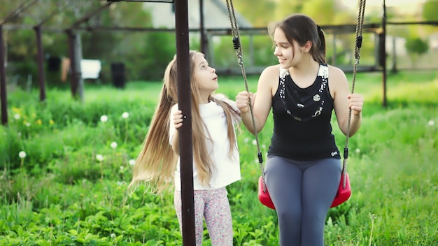 Cheerful happy two sisters in light spring clothes. have fun ride on a street red swing in a home blooming green garden and laugh in a wide smile