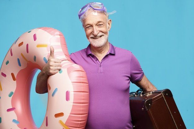 Веселый счастливый небритый мужчина-пенсионер проводит отпуск на пляже, одетый в летнюю футболку и маску для подводного плавания с аквалангом, держит чемодан и надувное кольцо для плавания, взволнованно улыбается