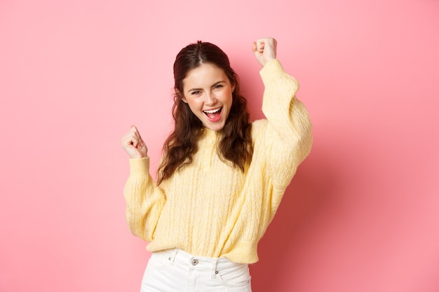 Cheerful happy woman achieve goal, celebrates success, saying yes and dancing, do victory champion dance, standing against pink wall.