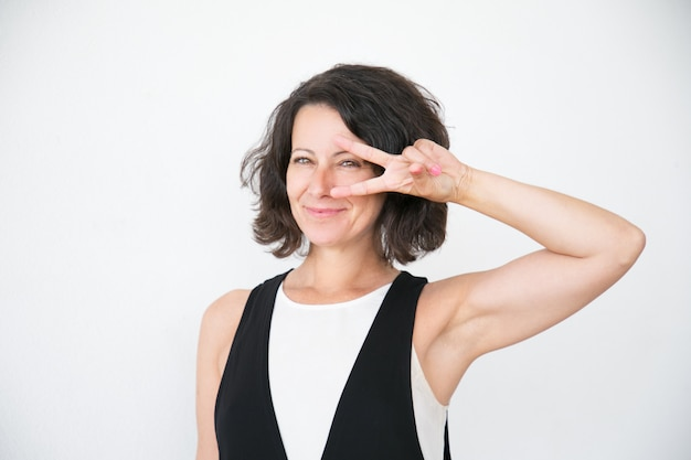 Cheerful happy woman in casual showing peace sign