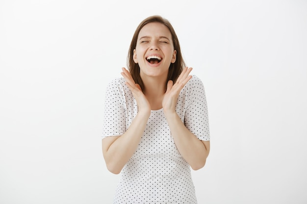 Веселая счастливая женщина празднует отличные новости, хлопает в ладоши и смеется от радости
