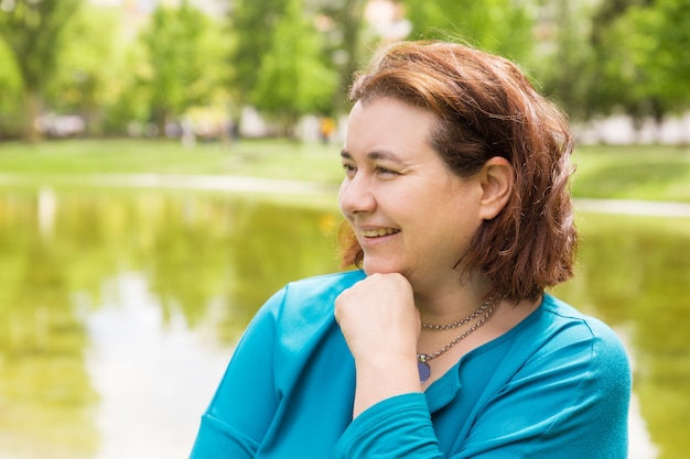 Cheerful happy woman leaning chin on hand