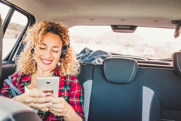 陽気な幸せな女性が携帯電話を使用してヘッドフォンで音楽を聴く現代の車の中の後部座席に座る