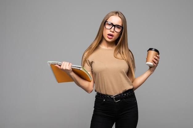 Веселая счастливая женщина с зубастой улыбкой несет кофе на вынос и красную книгу, рада закончить учебу, изолированную над поверхностью студии. люди, досуг и концепция питья