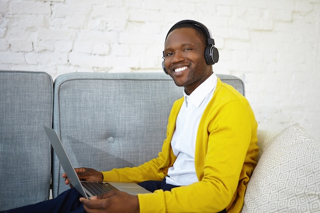 Cheerful happy young african american male in casual wear enjoying modern electronic devices at home, listening to favorite music using wireless headphones and laptop computer, relaxing on sofa