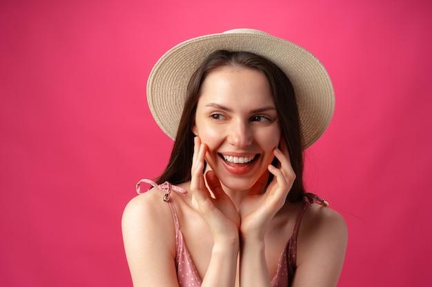 분홍색 배경에 웃고 웃고 있는 쾌활한 행복한 젊은 아름다운 소녀