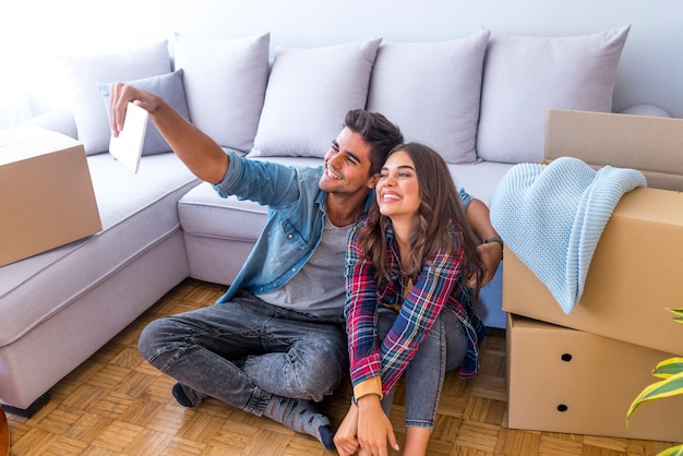 Cheerful and happy young couple making a selfie in new home with moving cardboard box duri