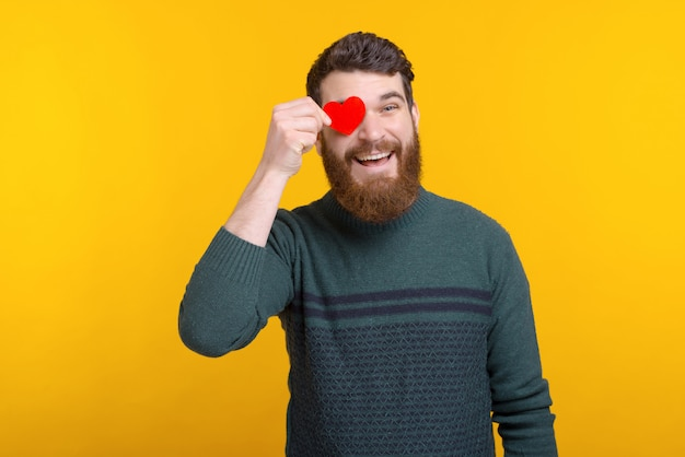 Cheerful happy young man holding red paper heart over his eyes