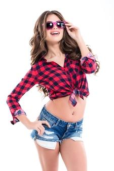 캐주얼 옷과 흰 벽 위에 서있는 분홍색 선글라스에 쾌활한 행복 한 젊은 여자