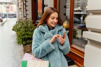 Cheerful happy young woman using smartphone and holding shopping bags.