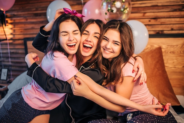 Cheerful and happy young women embracing each other. they sit on bed in room together and look. teenagers wear pajamas. they have home party.