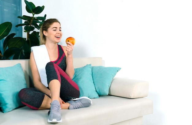 Cheerful healthy young woman sitting on sofa looking at red apple