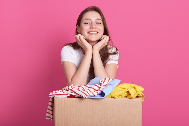 Cheerful helpful volunteer standing isolated over pink, holding box with clothes for secondary use, keeps hands under chin, looks at camera with pleased facial expression.