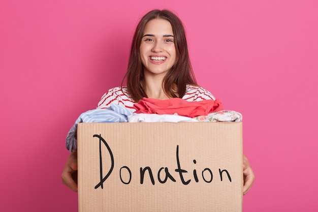 Cheerful helpful volunteer standing isolated over pink, holding box with inscription donation, full of donated clothes. smiling brunette woman being happy to do good things.