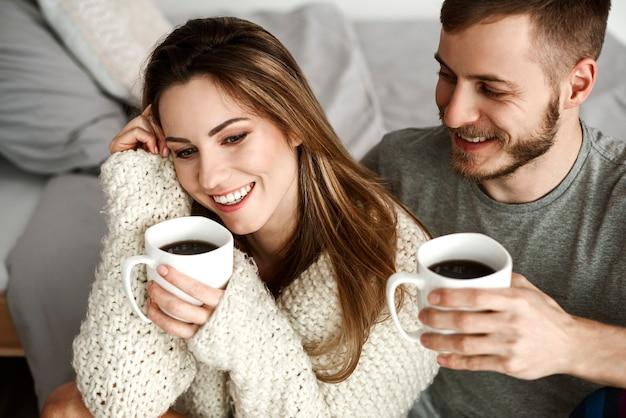 Веселая гетеросексуальная пара пьет кофе