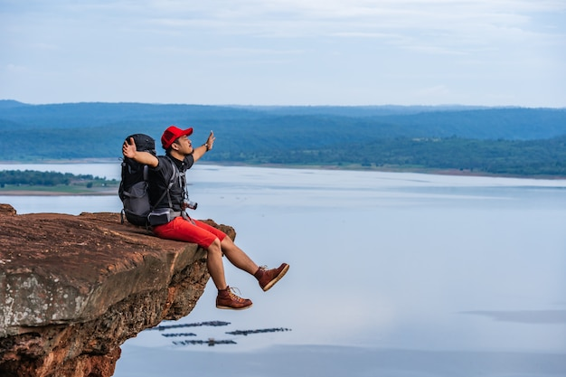 Cheerful hiker man sitting and gesture raised arms on the edge of cliff, on a top of the rock mountain