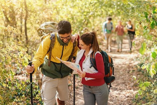 地図を見て正しい方法を探している陽気なハイカー。森の外観の秋の時間。
