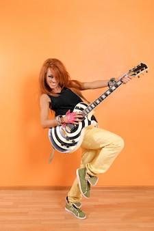 Веселая хип-хоп девушка с гитарой