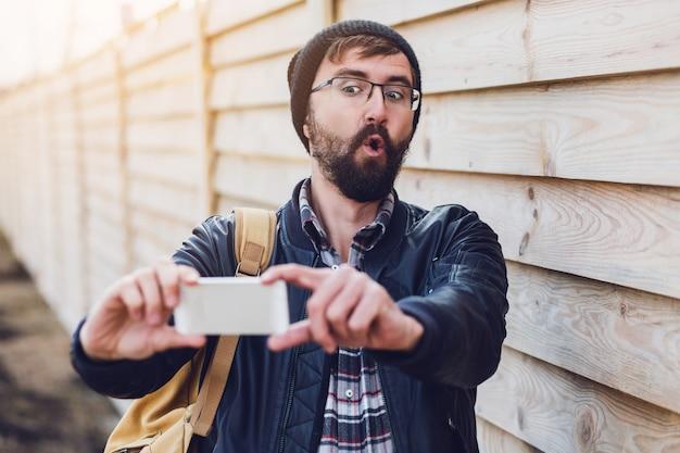 陽気な流行に敏感なひげ男笑顔と携帯電話でセルフポートレートを作る