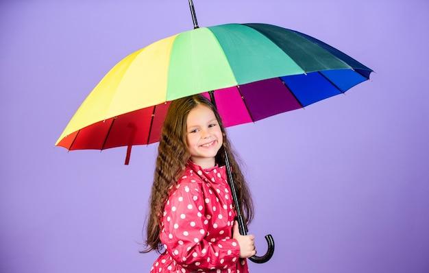 Веселый ребенок битник в позитивном настроении. защита от дождя. радуга. счастливая маленькая девочка с красочным зонтиком. маленькая девочка в плаще. осенняя мода. счастье подчеркивает ее красоту.