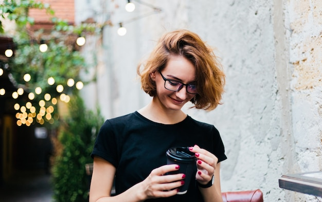 Cheerful hipster girl in glasses with short haircuts holding coffee cup