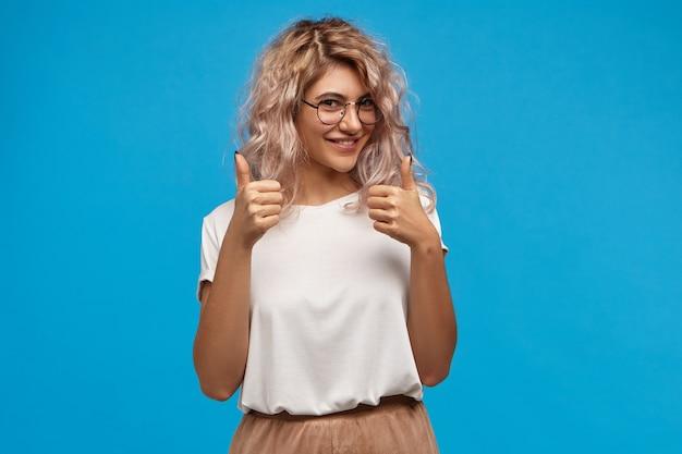 トレンディな丸いアイウェアを着た陽気なヒップスターの女の子が両手で親指を立てるジェスチャーをし、嬉しそうに笑って、誰かへのサポートと敬意を示して、よくやった、よくやった