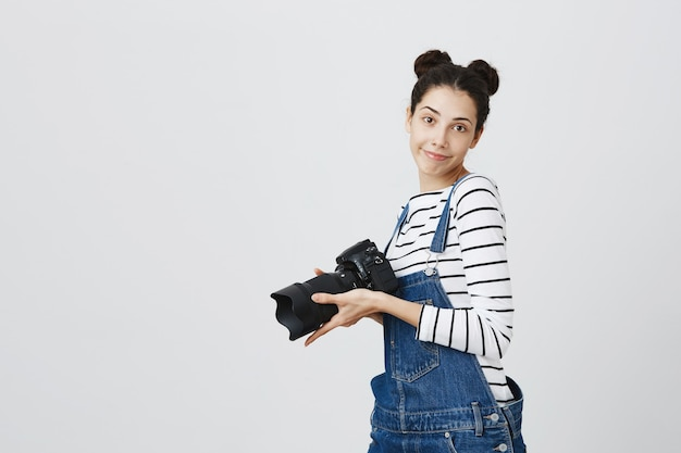 Cheerful hipster girl taking pictures on camera, photographing