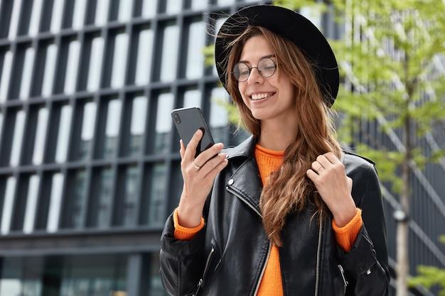 Cheerful hipster girl wears stylish black hat, leather jacket and round transparent spectacles