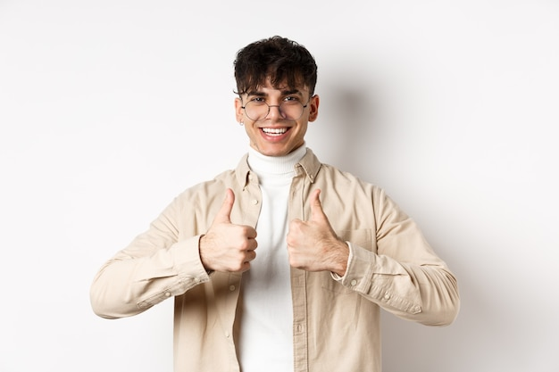 Cheerful hipster guy in glasses showing thumbs up and smiling, like good product, recommend or praise, standing on white wall.