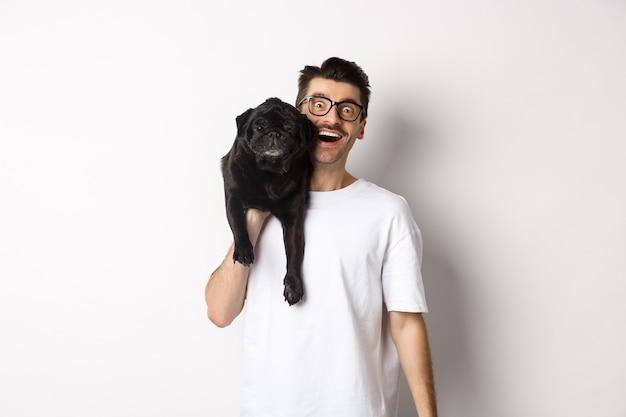 Cheerful hipster guy in glasses and t-shirt, carry cute black pug on shoulder and smiling. dog owner playing with his pet, standing over white.