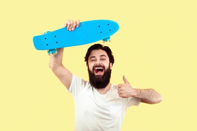 陽気な流行に敏感な男がスケートボードを持って、黄色の背景に、夏の気分の概念のように表示