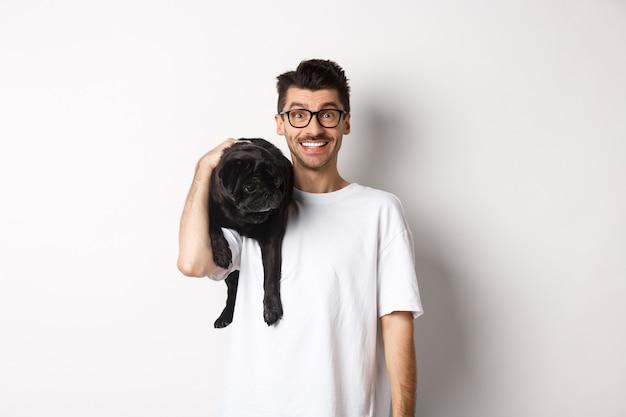 Веселый битник человек в очках, держа на плече симпатичную черную собаку мопса, глядя в камеру с счастливой улыбкой, стоя над белой.