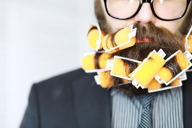 수염에 curlers와 쾌활 한 hipster 남자입니다. 안경을 쓴 놀란 남자가 앞을 본다.