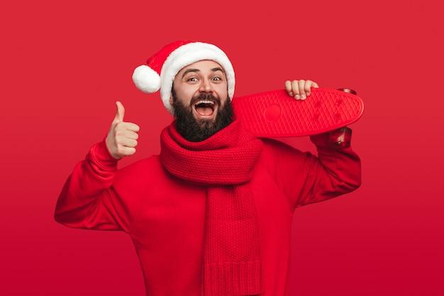 Веселый хипстер со скейтбордом, одобряющий рождественскую вечеринку