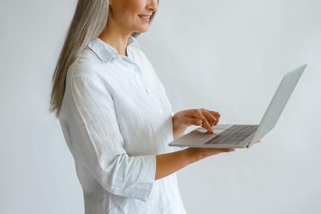 흰 블라우스를 입은 쾌활한 백발의 중년 여성은 스튜디오 측면 뷰 클로즈업에서 밝은 배경에 현대적인 노트북을 사용합니다